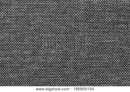 Dark gray shiny background of dense woven bagging fabric closeup. Structure of the steel cloth with natural texture. Cloth backdrop.