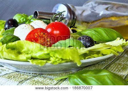 Caprese. Caprese salad. Italian salad. Mediterranean salad. Italian cuisine. Mediterranean cuisine. Tomato mozzarella basil leaves and olive oil on wooden table. Recipe - Ingredients