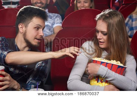 Couple watching movie at cinema, angry boyfriend pulling hand to popcorn and his greed girlfriend embracing big bucket and shouting. Man wanting eating tasty popcorn at cinema.