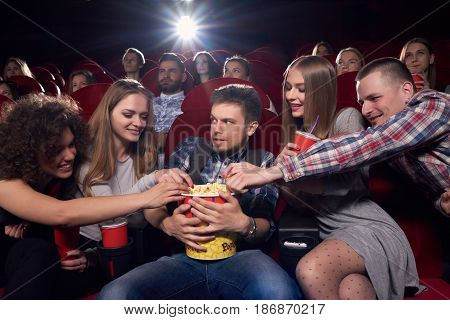 Group of friends watching movie and spending time at cinema, pulling hands to popcorn, greed man angry looking and embracing big bucket. Happy girl and boys wanting eating tasty popcorn at cinema.