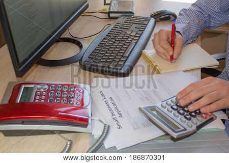 Business loans young entrepreneurs. closeup of a young man checking accounts with a calculator. Business loans with monthly payments