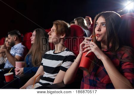Friends and couples, watching interesting film at big cinema hall with red chairs, serious looking at screen, thinking about movie and drinking cola. Concept of culture and entertainment.