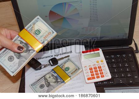 Car insurance form with car keys much dollars Laptop and calculator. Insurance concept