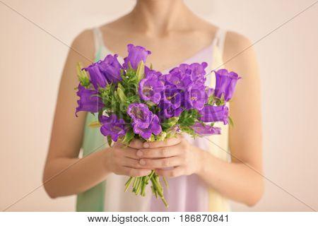 Woman holding beautiful bouquet of purple bellflowers on light background