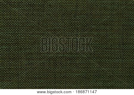 Dark green shiny background of dense woven bagging fabric closeup. Structure of the olive cloth with natural texture. Cloth backdrop.