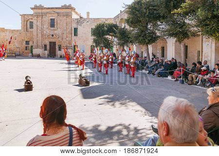 VALLETTA MALTA - February 21 2010 - Knights of the Order of St. John during reenactment. Tourists watch the performance from from the fenced places.