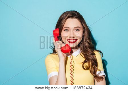 Close up portrait of a smiling pretty woman in dress holding retro telephone tube and looking at camera isolated over blue background