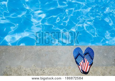 Summer background with heart of flip flops of American flag colors and pattern near the swimming pool