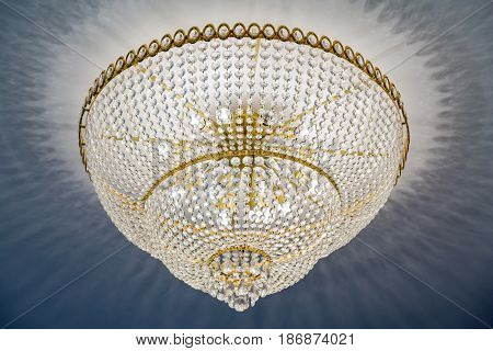 Crystal or glass chandelier on the ceiling with lights