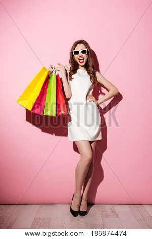 Picture of a cheerful young brunette woman in white summer dress wearing sunglasses posing with shopping bags and looking at camera over pink background.