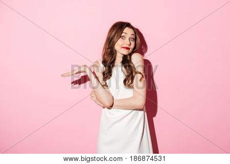 Portrait of a uncertain pretty woman shrugging shoulders isolated over pink background