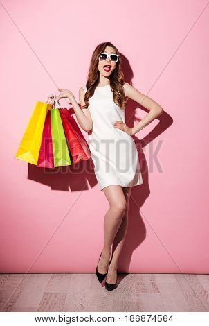 Image of a happy young brunette woman in white summer dress wearing sunglasses posing with shopping bags and looking at camera over pink background.