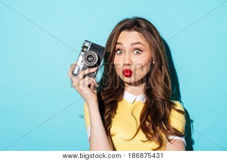 Portrait of a funny cute girl in dress holding vintage camera and looking at camera isolated over blue background