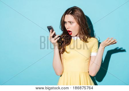 Portrait of a surprised confused woman in dress looking at mobile phone isolated over blue background