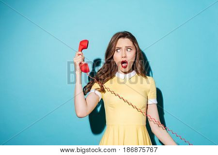 Portrait of a shocked surprised girl in dress talking on retro telephone tube and looking away at copyspace isolated over blue background