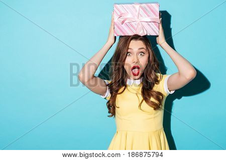 Portrait of a surprised shocked young woman in dress holding present box above her head isolated over blue background