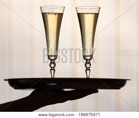 Champagne champagne flutes alcohol champagne glasses focus on foreground hand holding tray