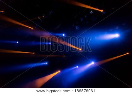 The blue-orange light from the spotlights through the smoke in the theatre during the performance. Lighting equipment.