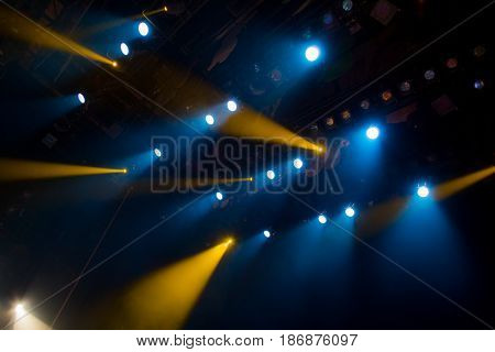 The blue-yellow light from the spotlights through the smoke in the theatre during the performance. Lighting equipment.