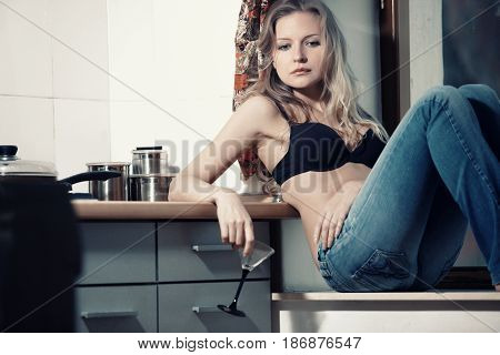 Single lady sitting at the kitchen with alcohol drinks