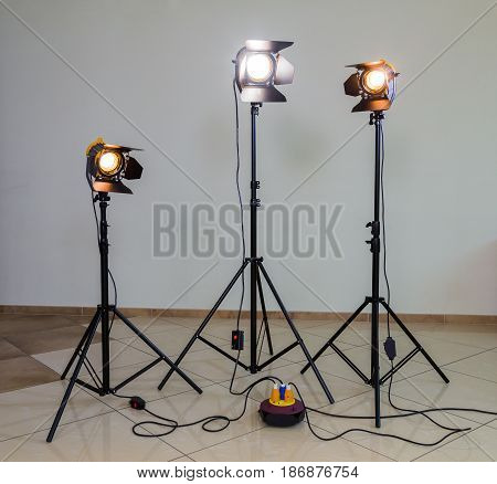 Three halogen spotlights with Fresnel lenses on a grey background. Photographing and filming in the interior. Lighting equipment for movie production.