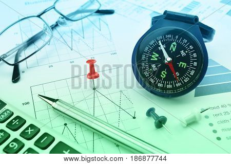 Blue compass calculator pen pin and glasses on graph paper Business success concept