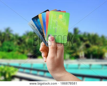 Travel concept. Woman holding credit cards and resort on background