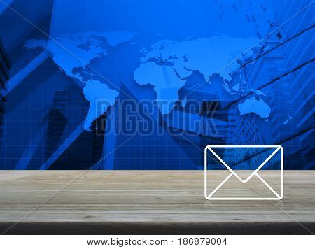 Mail icon on wooden table over world map and modern city tower Contact us concept Elements of this image furnished by NASA
