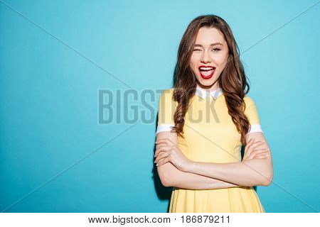Portrait of cheerful pretty woman in dress standing and winking with her arms crossed isolated over blue background