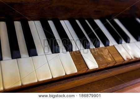 Soft focus of very old Piano with broken keyboards showing texture of wooden material