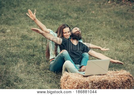 Happy Couple In Love With Flying Gesture And Laptop Outdoor