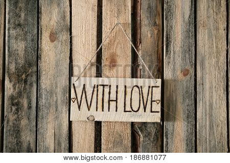 Plaque with the inscription WITH LOVE hangs in the middle on the background of wooden wall. Horizontal photo