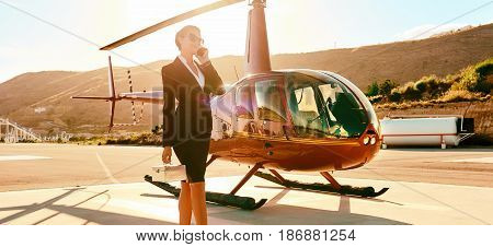 Elegant business woman talking by phone near the helicopter. Business success and luxury concept