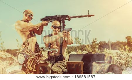 Two powerful bald soldiers with guns on the military tricycle.