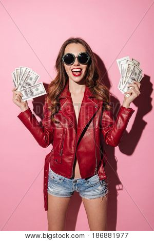 Portrait of a happy young girl in leather jacket holding money banknotes and shouting isolated over pink