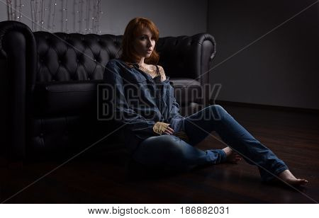 Portrait of a redhead girl in a jeans shirt and jeans sitting at the black sofa on the floor. Horizontal photo