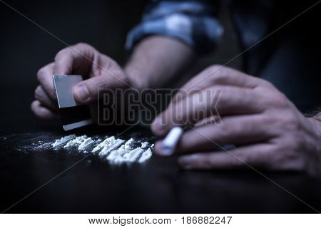 Few minutes before illegal action. Depressive exhausted young freak sitting in the dark room while preparing heroin lines and holding credit card
