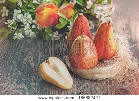 Still life of pears with flowers art on wooden background, toned