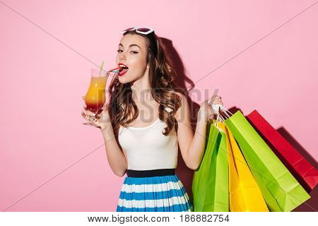 Portrait of a beautiful young girl shopaholic drinking cocktail and holding colorful shopping bags isolated over pink background