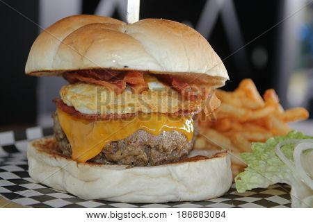 Big single cheeseburger with french fries  A serving of cheeseburger complete with eggs, bacon, ham and french fries