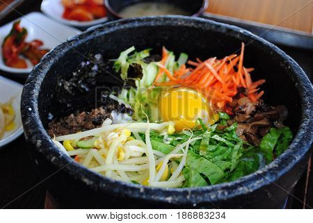 Bibimbap in a hot stone pot Bibimbap is a traditional Korean favorite made up of steamed rice, topped with meat, raw or fried egg and vegetables and usually served in a hot stone pot.