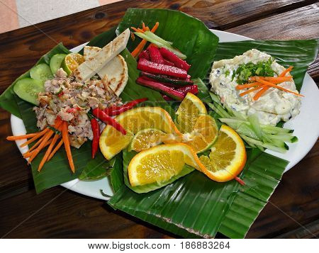 Chamorro- beef kelaguen and potato salad in banana leaves Favorite foods of Chamorros, people from the Northern Mariana Islands. Beef kelaguen  (raw beef cooked only with a marinate) with peppers and cucumber, potato salad, pickled radish and vegetables.