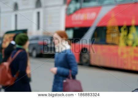 Blurred background with a young red women and  a red London double-decker