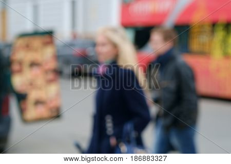 Blurred background with a young blond women and a man with  red London double decker