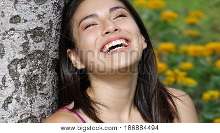 People Laughing and Sitting in a Meadow