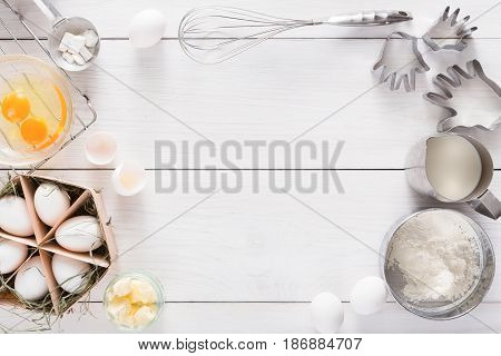 Baking background. Cooking ingredients for dough and pastry, eggs, flour and cookie cutter on white rustic wood. Top view with copy space, mockup for menu, recipe or culinary classes.