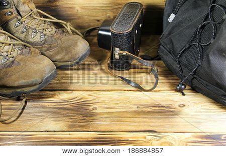 Set of traveler on wooden background. Old boots backpack and vintage photo camera in leather case. Travel concept
