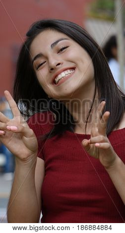 A Young Hispanic Happy Teen Girl Peace Gesture
