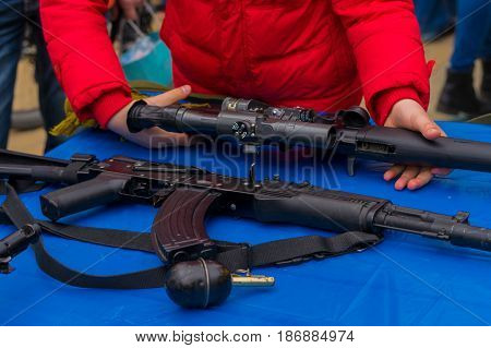 Weapons sniper rifle machine gun grenade Man Il the guy takes the sniper rifle the SVD in hand in the red jacket