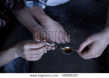 Preparing new opium dose . Addicted lonely homeless junkies siting in the darkness while preparing cocaine dose and using spoon and syringe